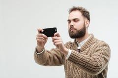 Hübsches junges erwachsenes nehmendes Foto mit seinem Smartphone lizenzfreies stockfoto