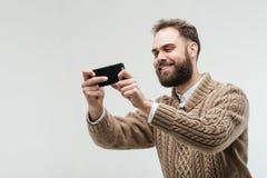 Hübsches junges erwachsenes nehmendes Foto mit seinem Smartphone lizenzfreies stockbild