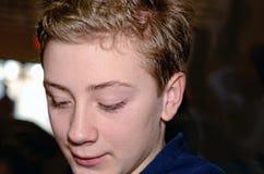 Hübsches junges jugendlich-Jungen-Porträt, das unten schaut stockbilder