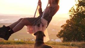 Hübsches junges Mädchen auf einem Schwingen während des überraschenden Sonnenuntergangs stock video footage
