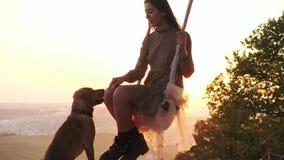 Hübsches junges Mädchen auf einem Schwingen während des überraschenden Sonnenuntergangs