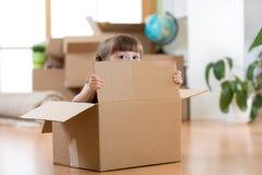 Hübsches Kind, das innerhalb eines Kastens nachdem dem Bewegen auf neue Wohnung sitzt Stockfotos