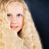 Hübsches Kindermädchen auf blauem Hintergrund Langes blondes Haar Stockfotos