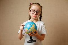 Hübsches Kindermädchen mit Gläsern zu Hause träumend von der Reise und vom Tourismus, die Weltkarte und die Kugel erforschend lizenzfreie stockfotografie