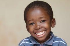 Hübsches kleines afrikanisches Junge Porträt, das mit toothy Lächeln lächelt Stockfotografie