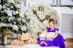 Hübsches kleines Mädchen 4 Jahre alt in einem blauen Kleid Baby im Weihnachtsraum mit teddybear, großer Uhr, Weihnachtsbaum, brau stockbilder