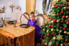 Hübsches kleines Mädchen 4 Jahre alt in einem blauen Kleid Das Kind am Tisch vor dem Weihnachtsessen stockbild