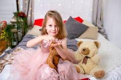 Hübsches kleines Mädchen 4 Jahre alt in einem rosa Kleid Kind im Weihnachtsraum mit einem Bett, Süßigkeit, Schokolade, Plätzchen  lizenzfreies stockfoto