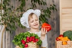 Hübsches Kleinkind in der Chefuniform mit Gemüse In der Küche zu Hause kochen vegetarier Gesunde Nahrung stockfotografie