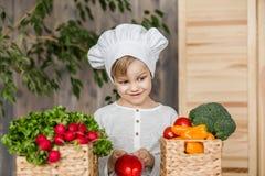 Hübsches Kleinkind in der Chefuniform mit Gemüse In der Küche zu Hause kochen vegetarier Gesunde Nahrung lizenzfreies stockbild