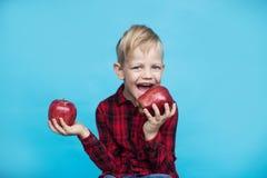 Hübsches Kleinkind mit Früchten Studioporträt über blauem Hintergrund lizenzfreies stockfoto