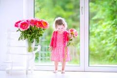Hübsches Kleinkindmädchen, das mit Pfingstrosenblumen spielt Lizenzfreie Stockfotografie
