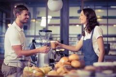 Hübsches lächelndes barista, das einen Kunden dient lizenzfreie stockbilder