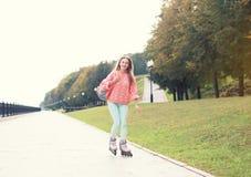 Hübsches lächelndes Mädchen, das im Stadtpark rollerblading ist Stockfotografie