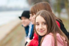 Hübsches lächelndes Mädchen draußen mit Freunden Stockfotografie