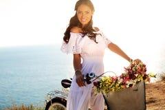 Hübsches lächelndes Mädchen mit dem dunklen Haar im eleganten Kleid, das auf Fahrrad sitzt Lizenzfreie Stockfotos