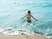 Hübsches lächelndes Mädchen in schäumenden Wellen von blauem Meer lizenzfreie stockfotos