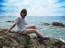 Hübsches lächelndes Mädchen sitzt auf dem Stein auf Seehintergrund lizenzfreie stockfotografie