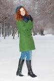 Hübsches lächelndes Mädchen wirft im Freien am Winter auf Stockbild