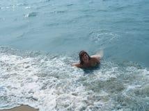Hübsches lachendes Mädchen in schäumenden Wellen von blauem Meer stockbilder