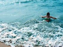 Hübsches lachendes Mädchen in schäumenden Wellen von blauem Meer lizenzfreies stockfoto