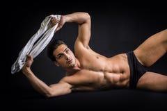 Hübsches lateinisches Legen des jungen Mannes nackt auf Boden Stockbild