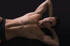 Hübsches lateinisches Legen des jungen Mannes nackt auf Boden Stockfotos