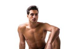 Hübsches lateinisches Sitzen des jungen Mannes nackt auf Boden, Lizenzfreies Stockbild