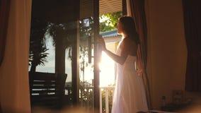 Hübsches Mädchen öffnet die Tür am frühen Morgen während des Sonnenaufgangs mit Blendenfleckeffekten und des Blickes heraus zur g Lizenzfreie Stockfotos