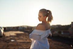 Hübsches Mädchen auf dem Dach, das im Sonnenlicht bei dem Sonnenuntergang steht stockfotografie