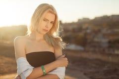 Hübsches Mädchen auf dem Dach, das im Sonnenlicht bei dem Sonnenuntergang steht Stockfoto