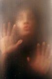 Hübsches Mädchen auf dem nassen Glas mit Tropfen des Regens Lizenzfreie Stockfotografie