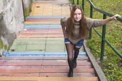 Hübsches Mädchen auf dem Stein tritt in die Stadt Lizenzfreie Stockfotografie