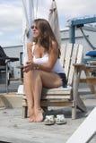 Hübsches Mädchen auf Dockside-Stuhl am mystischen Jachthafen stockfoto