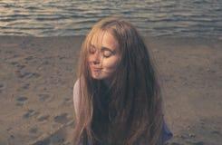 Hübsches Mädchen auf einem sandigen Seeufer, ihre Augen schloss Stockbild