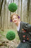 Hübsches Mädchen auf einem Schwingen im Wald mit dekorativen grünen Bällen Stockfotos