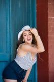 Hübsches Mädchen, das alte hölzerne blaue Tür lehnt Stockbild