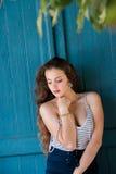 Hübsches Mädchen, das alte hölzerne blaue Tür lehnt Stockfoto