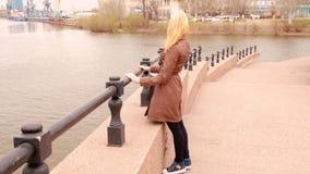 Hübsches Mädchen, das Ansicht des Hafens mit Kränen bei der Stellung betrachtet, lehnend auf Damm von Fluss in der Stadt stock video