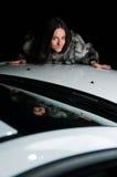 Hübsches Mädchen, das auf Autohaube legt Lizenzfreie Stockfotografie