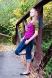 Hübsches Mädchen, das auf Brücke sich lehnt lizenzfreie stockbilder