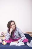 Hübsches Mädchen, das auf dem Bett sitzt Stockfoto