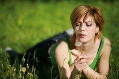 Hübsches Mädchen, das auf dem Gras durchbrennt einen Löwenzahn liegt Stockbilder