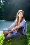 Hübsches Mädchen, das auf dem Gras im Sonnenschein sitzt Lizenzfreie Stockbilder