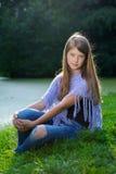 Hübsches Mädchen, das auf dem Gras sitzt Stockbild