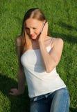 Hübsches Mädchen, das auf dem Rasen und der Unterhaltung sitzt Stockbild