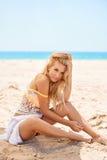 Hübsches Mädchen, das auf dem sandigen Strand sich entspannt Stockfotografie
