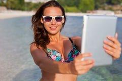 Hübsches Mädchen, das auf dem Strand steht und selfie durch ihre Tabelle nimmt Stockfotografie
