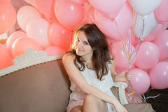 Hübsches Mädchen, das auf der Couch mit vielen Ballonen sitzt Stockbild
