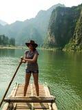 Hübsches Mädchen, das auf ein Bambusfloss schwimmt lizenzfreie stockbilder